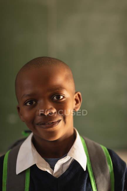 Ritratto da vicino di un giovane scolaro africano che indossa l'uniforme scolastica e lo zaino, guardando dritto davanti alla telecamera sorridente, in una scuola elementare cittadina — Foto stock