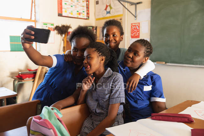 Vista frontale da primo piano di un gruppo di giovani studentesse africane che si divertono a posare e prendere selfie con uno smartphone durante una pausa dalle lezioni in una classe della scuola elementare township — Foto stock