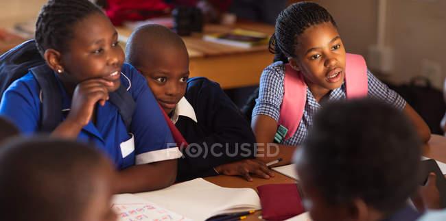 Plan rapproché de vue avant d'un groupe de jeunes écolières et écoliers africains socialisant ensemble pendant une pause des leçons dans une salle de classe d'école primaire de canton — Photo de stock