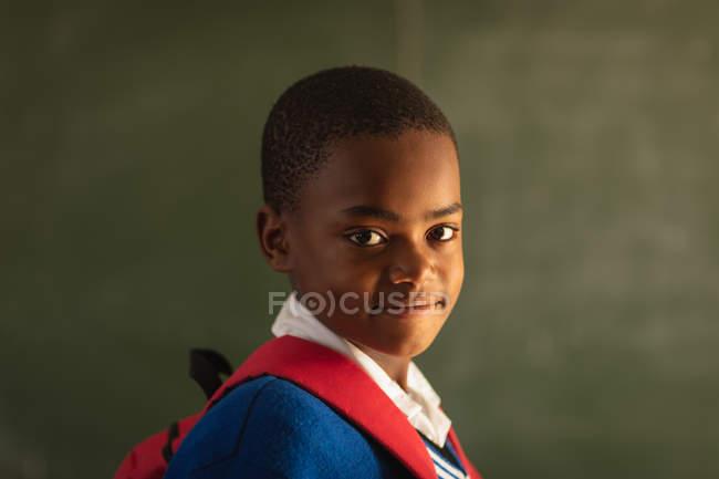 Retrato de cerca de un joven colegial africano vestido con su uniforme escolar y su mochila, mirando directamente a la cámara sonriendo, en una escuela primaria del municipio - foto de stock