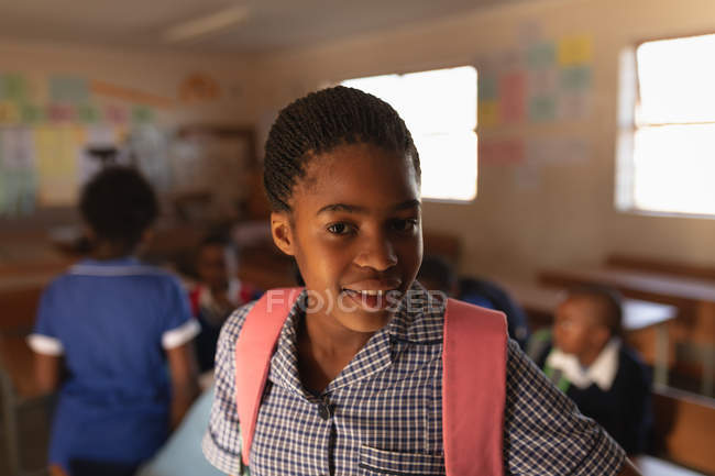 Portrait close up of a young African schoolgirl wearing her school uniform and schoolbag, looking straight to camera smiling, at a township elementary school with classmates in the background — Stock Photo