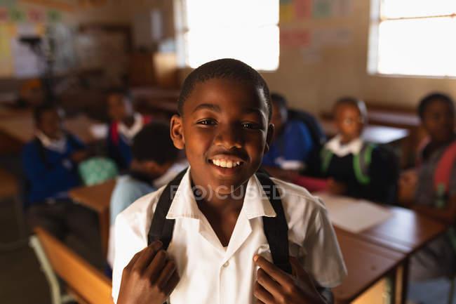 Verticale vers le haut d'un jeune écolier africain utilisant son uniforme d'école et un sac d'école, regardant directement à la caméra souriant, à une école primaire de canton avec des camarades de classe s'asseyant aux bureaux à l'arrière-plan — Photo de stock