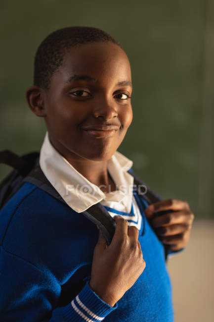 Retrato de cerca de un joven colegial africano con su uniforme escolar y su mochila, mirando directamente a la cámara sonriendo, en una escuela primaria del municipio - foto de stock