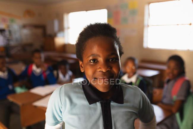 Verticale vers le haut d'une jeune écolière africaine utilisant son uniforme d'école et un sac d'école, regardant directement à la caméra souriant, à une école primaire de canton avec des camarades de classe s'asseyant aux bureaux à l'arrière-plan — Photo de stock