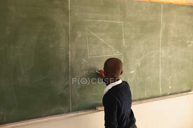 Vue arrière d'un jeune écolier africain restant à l'avant de la classe écrivant sur le tableau noir pendant une leçon dans une salle de classe d'école primaire de canton — Photo de stock
