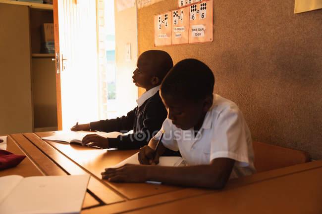 La vue de côté se ferment vers le haut de deux jeunes écoliers africains s'asseyant à un bureau travaillant pendant une leçon dans une salle de classe d'école primaire de canton — Photo de stock