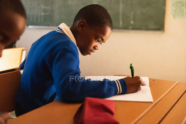 La vue de côté se ferment vers le haut d'un jeune écolier africain s'asseyant à un écriture de bureau pendant une leçon dans une salle de classe primaire d'école de canton — Photo de stock