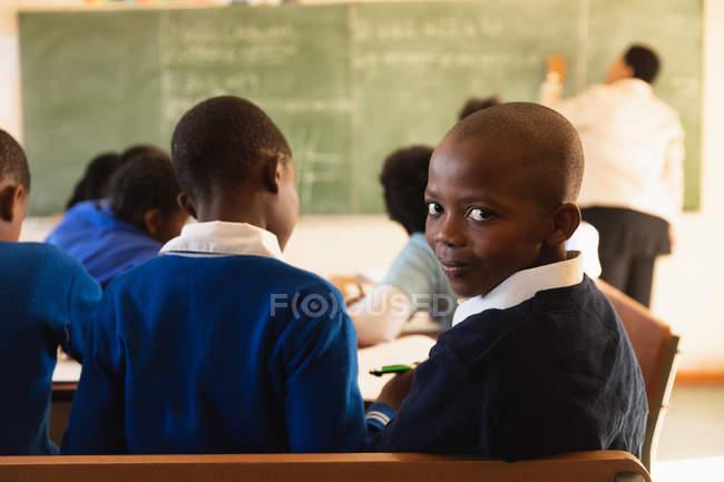 Vista lateral de cerca de un joven colegial africano sentado en su escritorio y dando la vuelta, mirando a la cámara y sonriendo durante una lección en un aula de la escuela primaria del municipio . - foto de stock