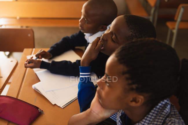 La vue de côté élevée se ferment vers le haut d'une jeune écolière africaine et de deux écoliers s'asseyant à des bureaux écoutant pendant une leçon dans une salle de classe d'école primaire de canton — Photo de stock