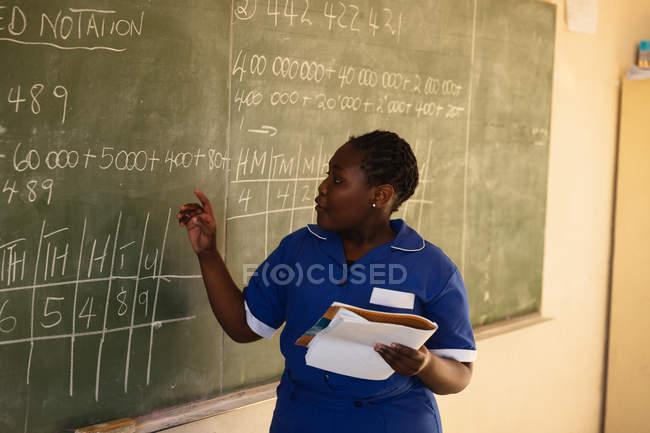 Вид спереду крупним планом молодого Африканського школярки стоячи на передній частині класу тримає книгу і писати на дошці під час уроку в селищі початкової школи класі — стокове фото