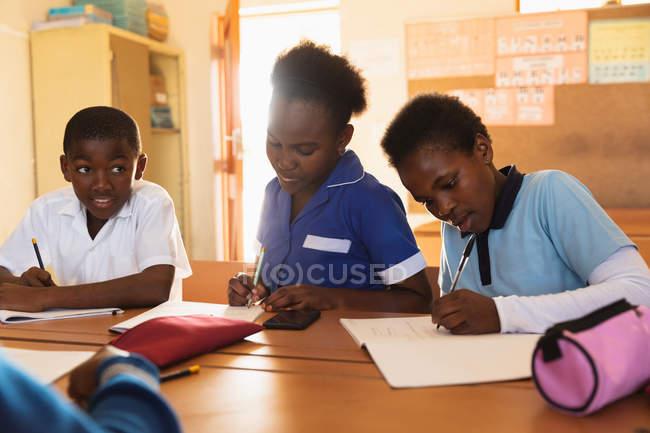 Вид на молодий Африканський школяр і два школярки сидять на столах письмово під час уроку у містечку початкової школи школі — стокове фото