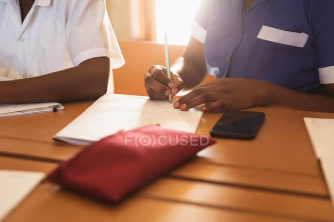 Середина секції молодого Африканського школяр і школярка сидять на столі письмово під час уроку в селищі початкової школи школі — стокове фото