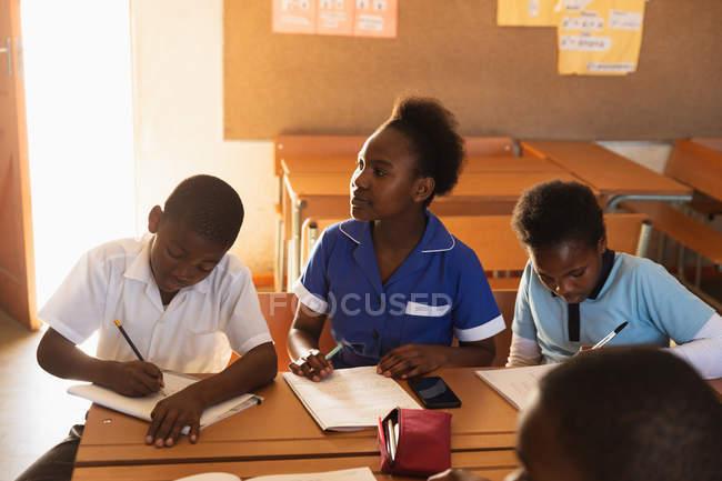 Vue avant d'un jeune écolier africain et de deux écolières s'asseyant aux bureaux écrivant pendant une leçon dans une salle de classe primaire de école de canton, une écolière regarde vers le point noir — Photo de stock