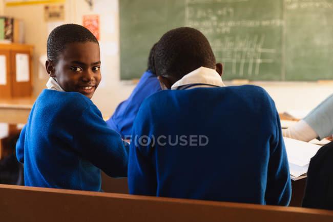 La vue de côté se ferment vers le haut d'un jeune écolier africain s'asseyant à son bureau et se retournant, regardant à l'appareil-photo et souriant pendant une leçon. — Photo de stock