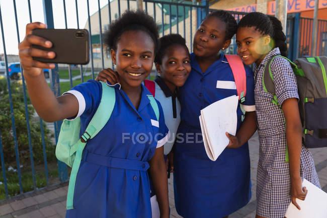 Fim da vista dianteira acima de um grupo de alunas africanos novos que têm o divertimento que levanta e que toma selfies com um smartphone em um campo de jogos da escola elementar do Township — Fotografia de Stock