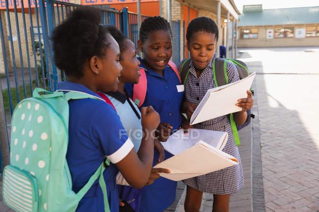 Fim da vista lateral acima de quatro estudantes africanos novos que desgastam schoolbags, olhando livros de escola no campo de jogos de uma escola elementar do Township — Fotografia de Stock