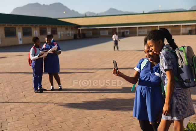 Opinião lateral duas alunas africanas novas que olham um smartphone junto em um campo de jogos da escola elementar do Township. No fundo dois de seus colegas estão olhando seus livros de escola — Fotografia de Stock