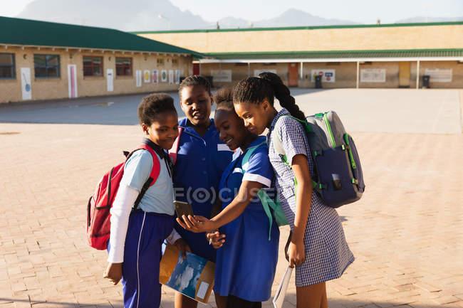 Fim da vista dianteira acima de um grupo de estudantes africanos novos que olham um smartphone junto em um campo de jogos da escola elementar do Township — Fotografia de Stock