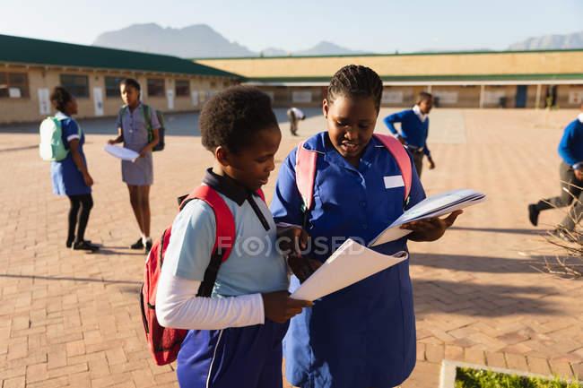 Fim da vista lateral acima de duas alunas africanas novas que desgastam schoolbags, olhando um livro de escola no campo de jogos de uma escola elementar do Township. — Fotografia de Stock