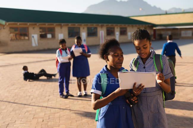 Fim da vista dianteira acima de duas alunas africanas novas que desgastam schoolbags, olhando um livro de escola no campo de jogos de uma escola elementar do Township. — Fotografia de Stock