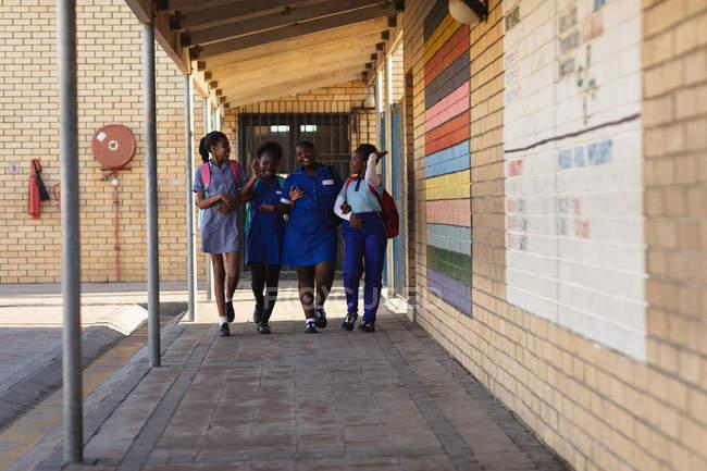 A vista dianteira de quatro alunas africanos novos que desgastam mochilas que sorriem e que andam com braços lig no campo de jogos de uma escola elementar do Township — Fotografia de Stock