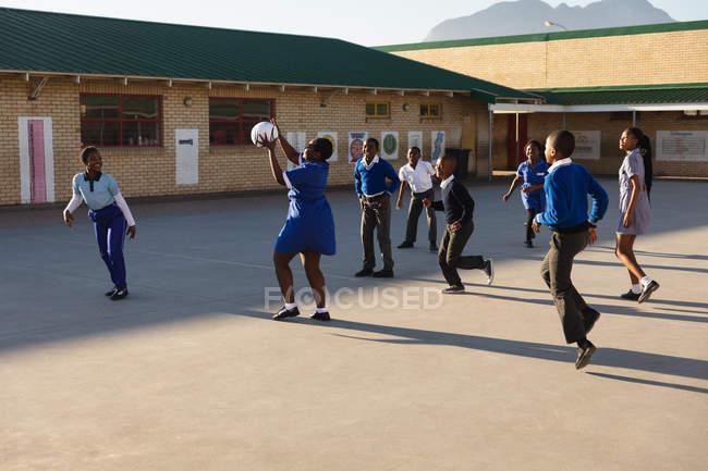 Vista laterale di un gruppo di giovani studentesse africane e scolari che saltano e giocano con una palla nel parco giochi di una scuola elementare township — Foto stock