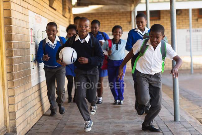 Vista frontal close-up de um grupo de jovens escolares africanos correndo no pátio da escola com mochilas escolares e uma bola de futebol em uma escola primária da cidade — Fotografia de Stock