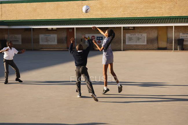 Vista posteriore di una giovane studentessa africana e due scolari che saltano e giocano con una palla nel parco giochi di una scuola elementare township — Foto stock