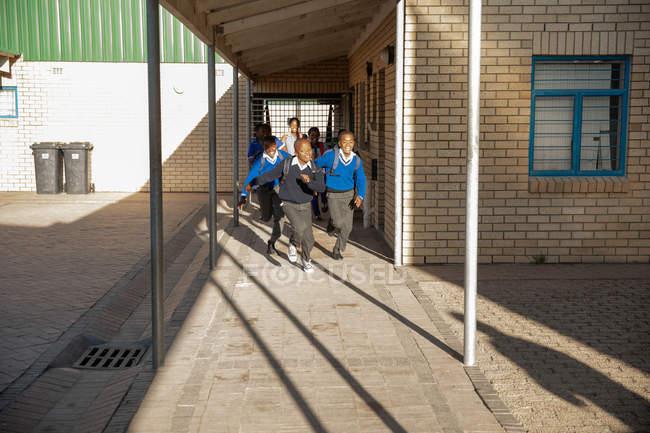 Vista frontale di due giovani scolari africani che esauriscono la scuola e nel cortile della scuola davanti all'insegnante e ai loro compagni di classe in una scuola elementare di township — Foto stock