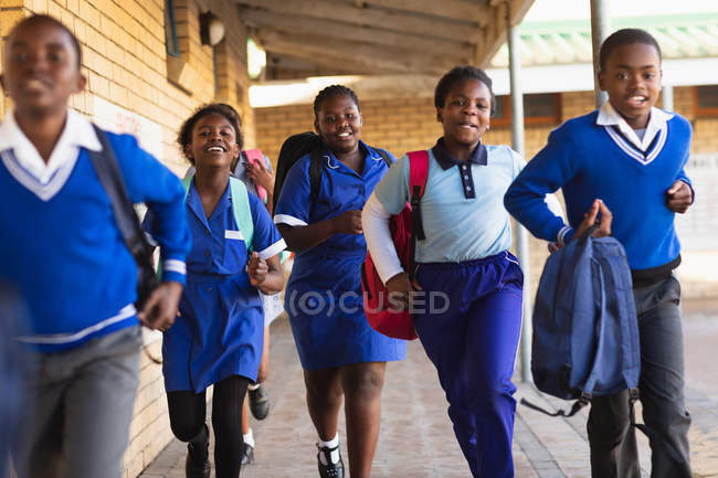 Vista frontale da vicino di giovani scolari africani e studentesse che corrono nel cortile della scuola portando borse in una scuola elementare township — Foto stock