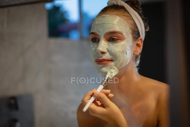 Крупный план отражения молодой кавказской женщины, смотрящей в зеркало и надевающей маску . — стоковое фото
