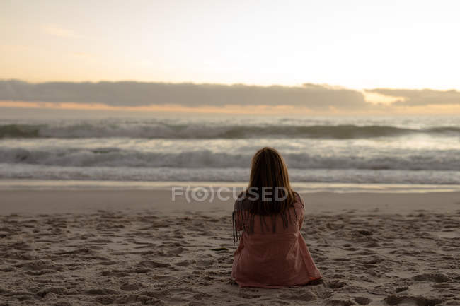 Rear view of a mature Caucasian woman sitting on a beach facing the sea at sunset — Stock Photo