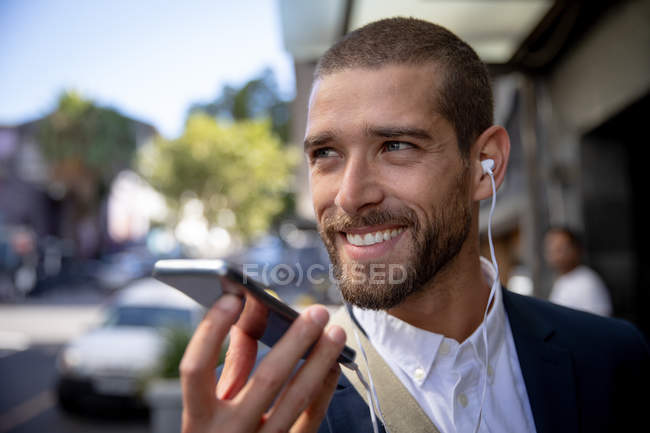 Front view close up of a smiling young Caucasian man talking on a smartphone holding it in front of his face and wearing earphones in a city street. Digital Nomad on the go. — Stock Photo