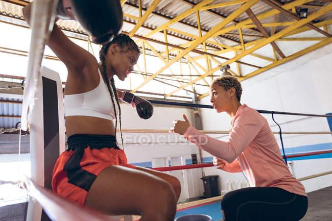 Trainer interagiert mit Boxerin im Boxring im Fitnesscenter. Starke Kämpferin im Box-Fitness-Training hart. — Stockfoto