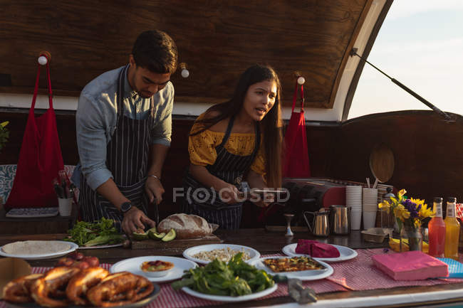 Front view close up of a young mixed race couple busy preparing and serving food standing in an open top van offering a range of takeaway food for sale — Stock Photo