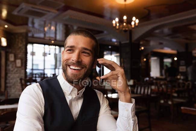 Vue de face gros plan d'un jeune homme caucasien souriant lors d'un appel téléphonique assis à une table à l'intérieur d'un café. Nomade numérique en mouvement . — Photo de stock