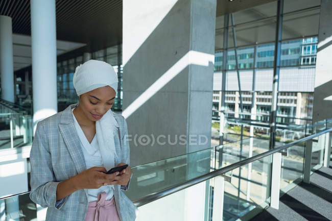 Happy businesswoman in hijab leaning on railing and using mobile phone in corridor at modern office — Stock Photo