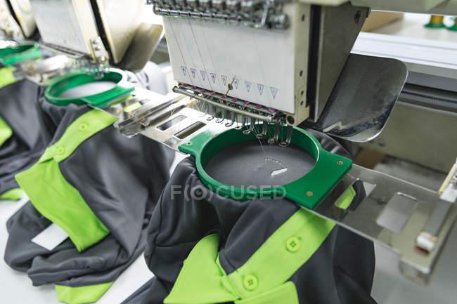 Крупним планом автоматизованих швейних машинок зшиваючи сорочки на фабриці спортивного одягу. — стокове фото