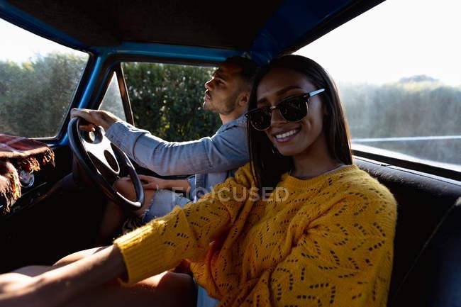 Крупним планом з бічним видом молоді змішані пари раси сидячи в їх пікап вантажівка під час поїздки дорозі. Людина водіння і жінка перетворюється на камеру і посміхається — стокове фото