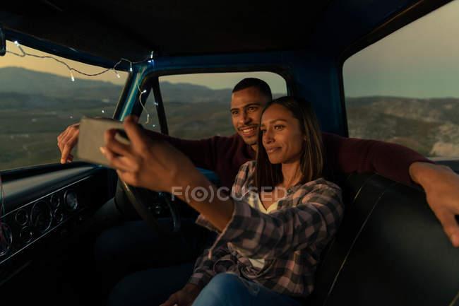 Вид спереди улыбающейся молодой смешанной расы, сидящей в машине, делая селфи в сумерках, во время остановки в дороге. Интерьер автомобиля освещается струнными огнями . — стоковое фото