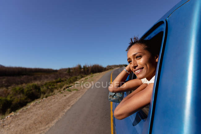 Vue latérale d'une jeune femme de race mixte penchée par la fenêtre avant côté passager d'une camionnette souriante, alors qu'elle descend l'autoroute lors d'un voyage en voiture — Photo de stock