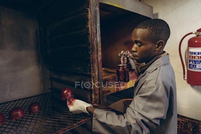 Вид збоку крупним планом молодого афро-американського людини, стоячи в області живопису проведення форми зовнішньої половини Червоної кулі крикет шкіри і спрей гармати в майстерні на заводі рішень крикет. — стокове фото