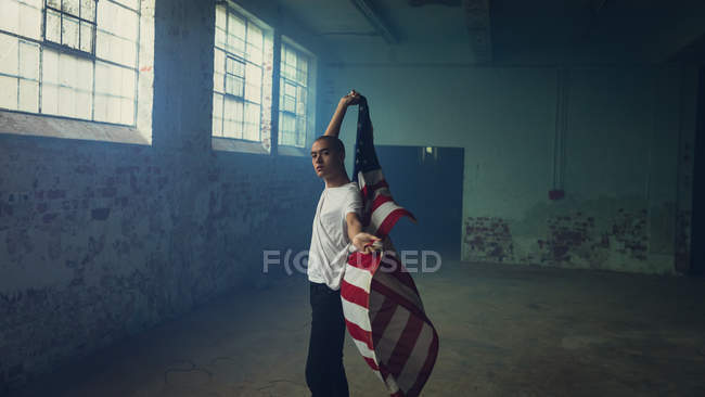 Side view of a young Hispanic-American man wearing a plain white shirt holding an American flag inside an empty warehouse — Stock Photo