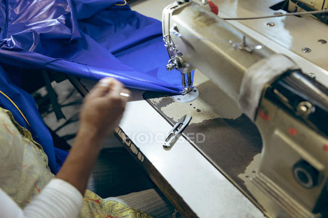 Close up of the hand of woman sewing with a sewing machine and blue fabric at a sports clothing factory. — Stock Photo