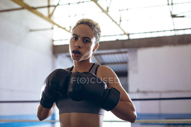 Close-up of female boxer practicing boxing in boxing club. Strong female fighter in boxing gym training hard. — стокове фото