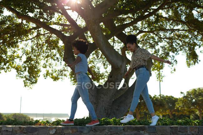 Side view close up of two young smiling adult mixed race sisters walking along a wall in an urban park, with their electric scooters parked below them — Stock Photo