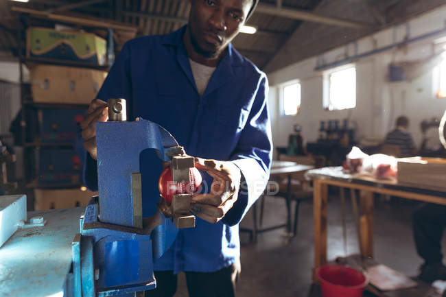 Front view close up of a young African American man working in a factory making cricket balls, holding a cricket ball in a vice and looking to camera. — стокове фото