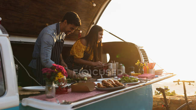 Side view of a young mixed race couple busy preparing and serving food standing in an open top van offering a range of takeaway food for sale — Stock Photo
