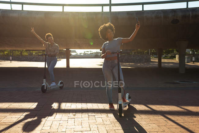 Front view of two young adult mixed race sisters riding on electric scooters in an urban park, one holding up a smartphone to take selfies of them, the other with her hand in the air making a peace sign for the picture, backlit with lens flare — Stock Photo