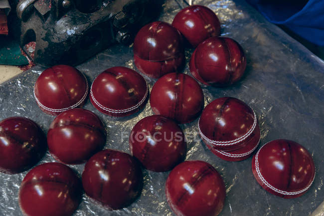 Підвищений крупним планом формуються зовнішні половинки червоних кульок крикет на виробничій лінії в майстерні на фабриці спортивного обладнання. — стокове фото